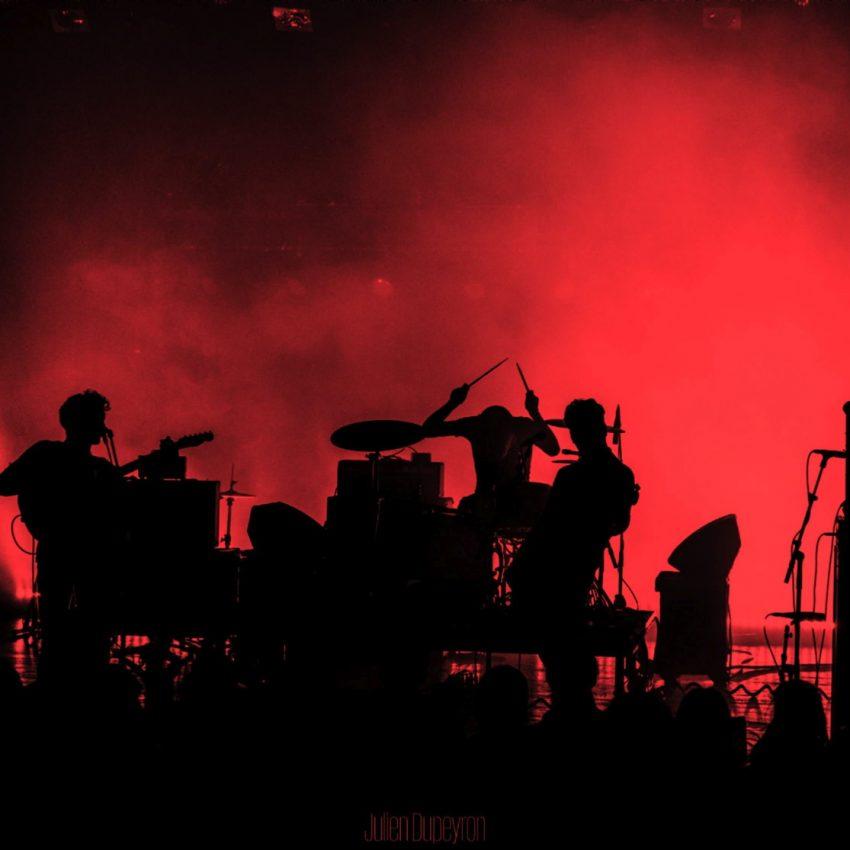 Photo des 3 musiciens sur scène en clair obscur sur fond de lumière rouge