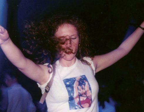 Jeune fille aux cheveux bouclés portant un tee-shirt manga qui danse dans la greenroom aux Trans Musicales 1995 lors d'une soirée Planète