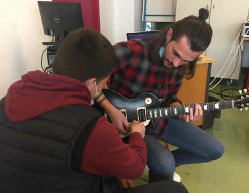 Un jeune élève fait bouger les cordes de la guitare tenue par Alvan