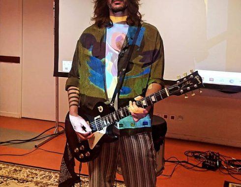 Alvan joue de la guitare face à la projection de son clip